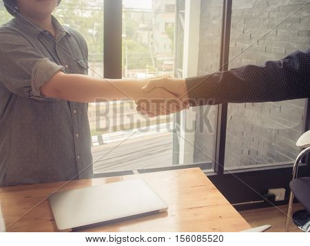 Business woman and partner shaking hands in office. vintage filter effect.