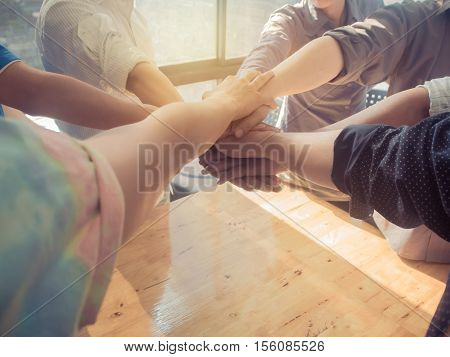 Group of people putting their hands working together on wooden background in office. group support teamwork cooperation concept. vintage.
