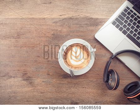 Laptop computer with cup of coffee and headphones on old wooden table with copy space. vintage filter effect.