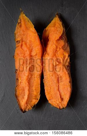 high-angle shot of a roasted sweet potato cut in half with a funny shape placed on a rustic gray surface