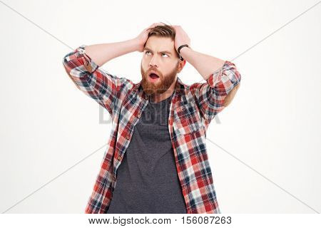 Frustrated casual man in plaid shirt with hands on his head looking away isolated on a white background