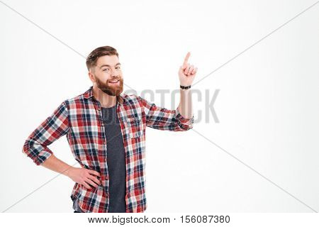 Smiling casual man in plaid shirt pointing finger up at copyspace over white background