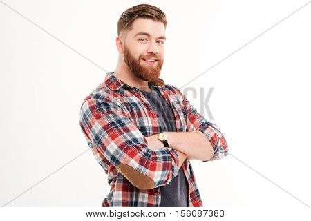 Portrait of a cheerful casual man in plaid shirt with arms folded looking at camera isolated on a white background
