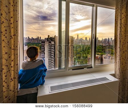 A little boy admiring the sunrise over Central Park with a view of Upper West Side and Upper East Side New York City New York City