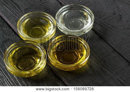 Different types of vegetable oil of vegetable mustard and sesame seed walnut grape seeds in glass bowls. It is used in dietary and healthy nutrition. Source of vitamins polyunsaturated fatty acids