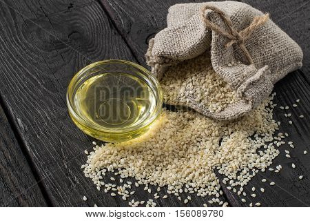 Sesame seeds in a linen bag and sesame oil in a bowl. It is used in dietary and healthy nutrition cosmetics herbal medicine. The source of vitamins and polyunsaturated fatty acids