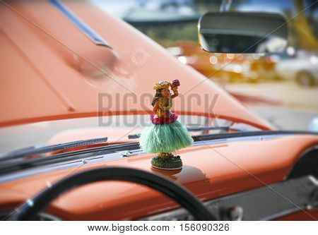 Hula girl statuette on dashboard of a vintage antique car