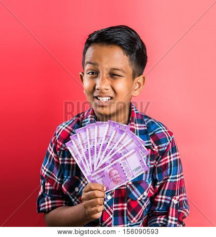 indian kid holding currency notes, indian kid and money, indian kid with 200 rupee note fan, indian kid holding currency note fan,five hundred rupee notes, new currency 2000 rupee note