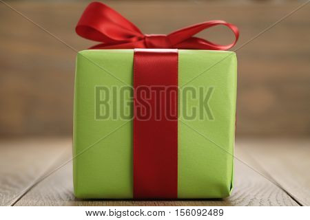 green paper gift box with classic red ribbon bow on wooden table closeup with shallow focus