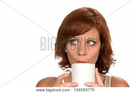 Redheaded woman blows into her coffee mug to cool it while looking up and thinking.