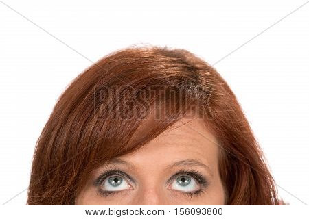 Top half of a redheaded woman as she looks up as a concept for thinking thoughts and ideas.
