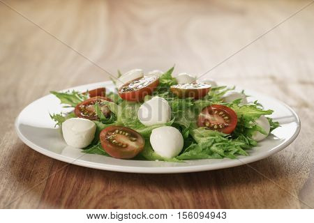 salad with kumato tomato, mozzarella and frillies lettuce, shallow focus