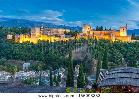 Moorish palace and fortress complex Alhambra with Comares Tower, Alcazaba, Palacios Nazaries and Palace of Charles V and roofs of Albayzin during evening blue hour in Granada, Andalusia, Spain