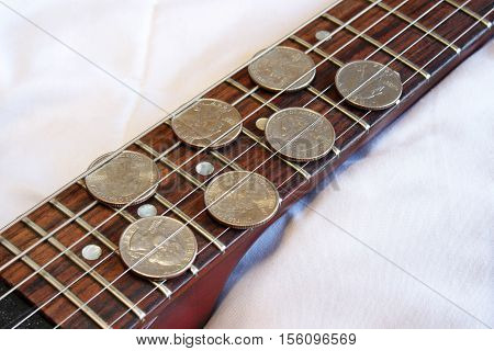 Quarters on guitar fretboard - Exaggeration of a struggling amateur musician's measly income