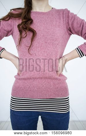 Slim young girl standing with arms akimbo on a white background