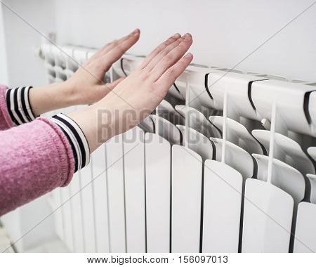 Girl warms the frozen hands above a hot of the radiator close up