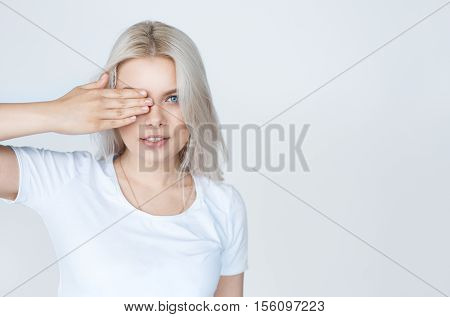 Closeup portrait of sexy whiteheaded young woman with beautiful blue eyes on white background with copy space. Girl covering her eye with a hand