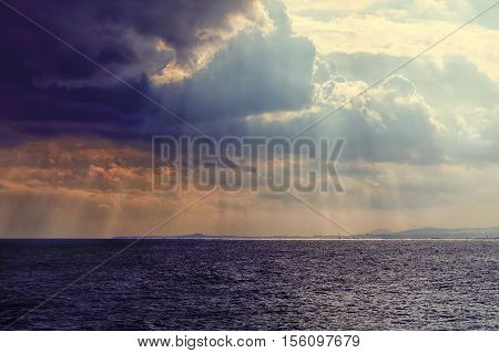 Sea landscape with bad weather and the cloudy sky. Dramatic cloudy sunset with sunbeams.