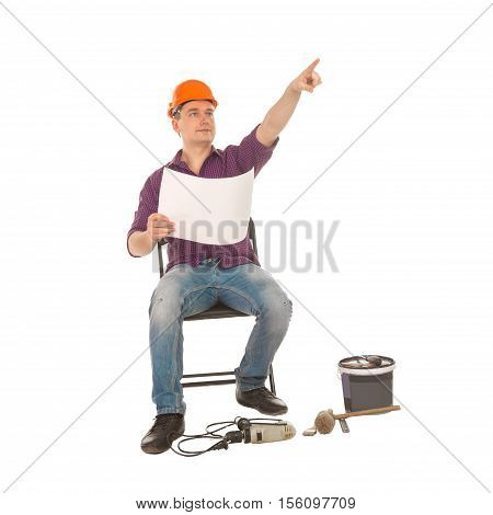 cheerful male construction worker with plan in his hands and scattered around tools sitting on a chair and pointing at something