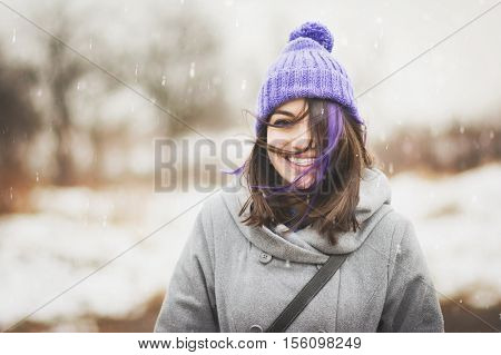 Portrait of cute, happy young woman in purple knitted beanie hat and gray coat, outdoors in winter on windy and snowy day, smiling and posing. Noise added for artistic effects.