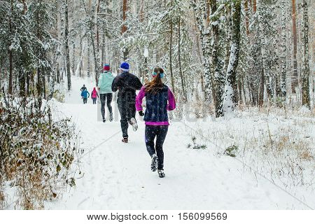 group of runners running in winter forest marathon in falling snow