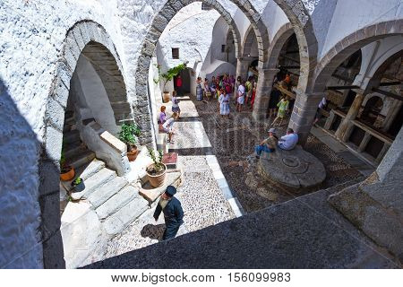 Patmos Greece - May 16 2010: A priest and visitors in the Agios Joannis Theologos Monastry