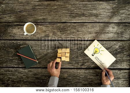 Conceptual image of business vision and innovation with an overhead view of a businessman sitting at a rustic table with building blocks and a hand drawn lightbulb on paper with text Vision.