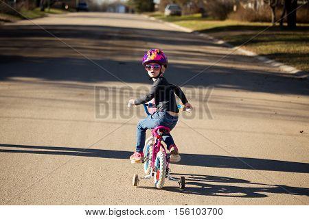 Little girl wearing a helmet riding her bike with training wheels down a street