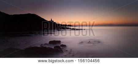 Sunrise at Bracelet Bay overlooking the Mumbles Lighthouse in Swansea Bay, South Wales