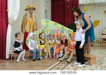 BALASHIKHA RUSSIA - OCTOBER 26: Eight small children dressed in carnival costumes and two adult women taking part in autumnal matinee in kindergarten on Zarechnaya Street on October 26 2016 in Balashikha.