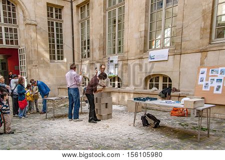 PARIS, FRANCE. Circa april 2016. Exhibition of artisans stone sculptor of the association rempart making a sculpture in stone in Paris