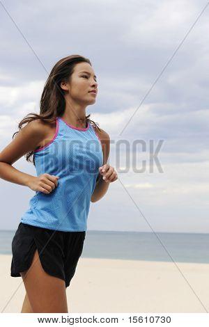 happy female runner running outdoors at the beach