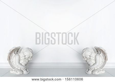 Statues of Sleeping Cupids on white background with copy space for text.