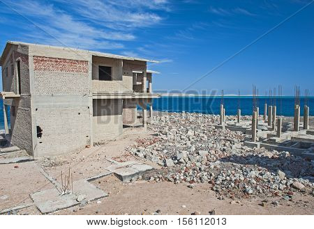 Half finished residence house on an abandoned building site at a coastal beach plot