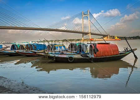 Wooden fishing boats lined up at Princep Ghat on river Hooghly with Vidyasagar Setu (bridge) at the backdrop.