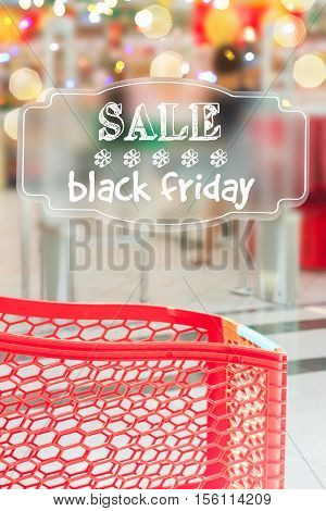 red cart in supermarket store with sale black friday text and shopping cart