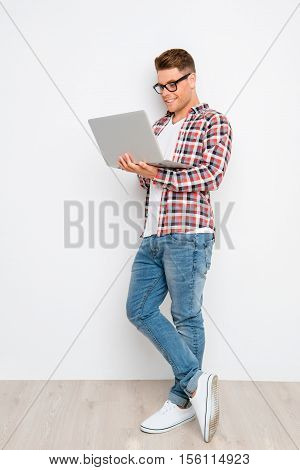 Full Photo Of Young Blogger Walking On Laptop Against White Wall