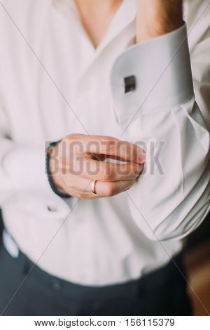 Elegant young fashion man in white shirt looking fixing his cufflinks.