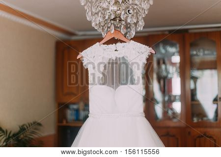 Luxurious wedding dress hanging on luster at dressing room.