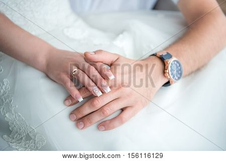 Hands newlyweds with a bouquetA newly weding couple place their hands on a wedding bouquet