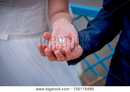 Hands newlyweds with a kay. newly weding couple place their hands on a wedding bouquet