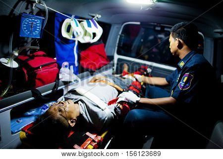 EMT and injured from motocycle accident inside an ambulance on their way to nearest hospital February 07 2010. This is the case of motocycle vs motocycle. This EMT is part of Sawang Prateep Volunteer Rescue Team. Sawang Prateep is one of many volunteer or