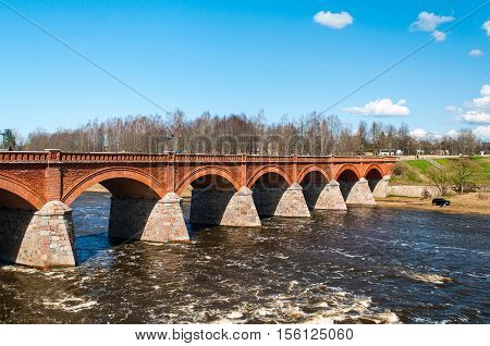 Old orange brick bridge over river Venta in Kuldiga town, Latvia
