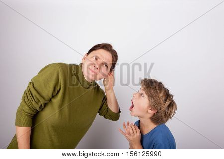 Mother cupping her hand behind ear can't hear her son