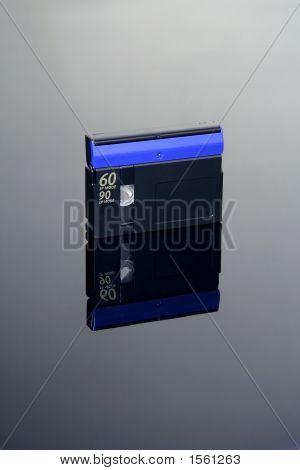 black mini DV tape on black reflective background poster