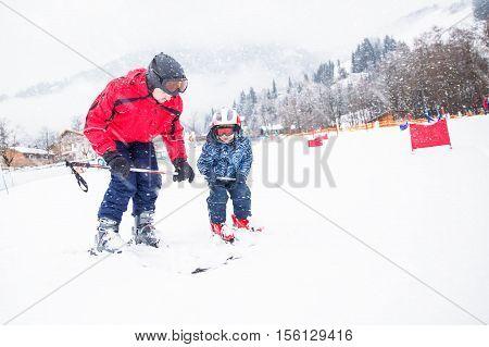 Father teaching skiing his little son in Kitzbuhel ski resort, Tyrolian Alps, Austria