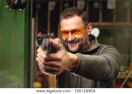 Shooting a gun at shooting range .