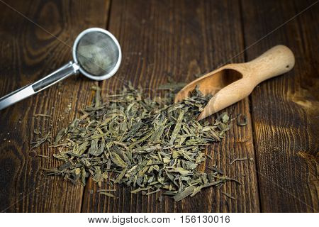 Heap of dried tea with strainer on natural wooden background.