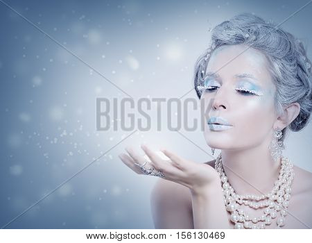 Winter Woman Fashion Model Blowing Snow at Night. Snow Queen Girl on Blue Background with Stars, Snow and Glitters