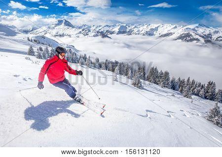 Young happy attractive man skiing in Kitzbuhel ski resort Tyrolian Alps Austria